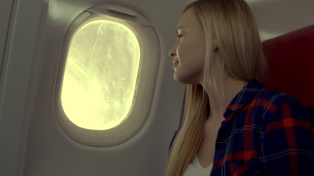 On-a-Plane-Beautiful-Blonde-Girl-Looks-out-of-the-Window-Sun-is-Shining-on-Her-and-She-Smiles-