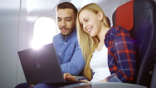 On-a-Board-of-Commercial-Airplane-Beautiful-Young-Blonde-with-Handsome-Hispanic-Male-Watch-Movies-on-a-Laptop-and-Laugh-Sun-Shines-Through-Aeroplane-Window-