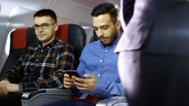On-a-Commercial-Flight-Young-Hispanic-Male-Uses-Smartphone-while-His-Neighbor-Looks-out-of-the-Window-Senior-Man-in-the-Back-Sleeps-Peacefully-