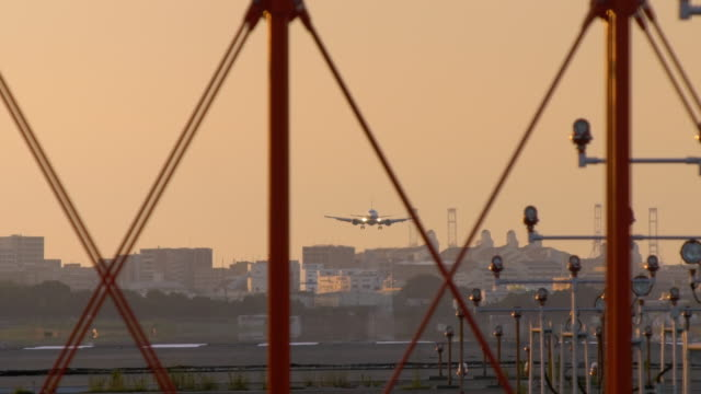 Airplane-landing-over-summer-sky-in-sunset-closeup-real-time