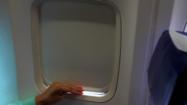 Primer-plano-de-mano-mujer-abre-y-cierra-el-obturador-de-la-ventana-del-avión