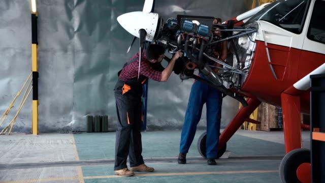 Dos-mecánicos-trabajando-en-un-avión-pequeño