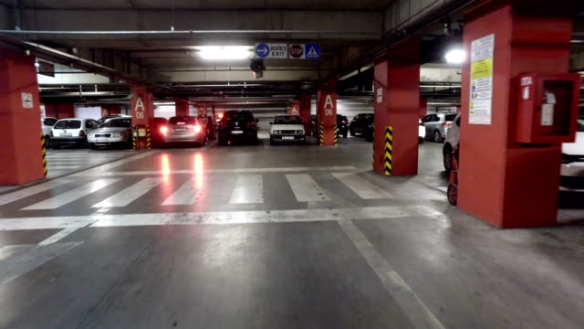 Moving-pov-at-underground-parking-lot-in-large-building-shopping-mall