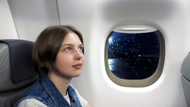 Young-woman-looking-through-window-in-airplane