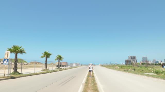 Girl-walks-on-road-near-coastline-and-barbed-fence-of-airport-in-Batumi-Georgia