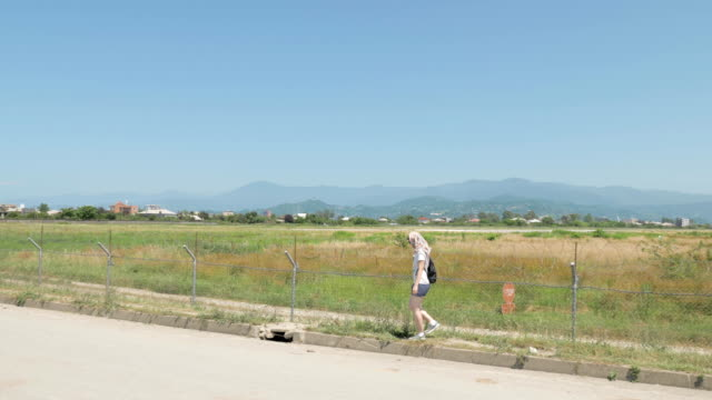 Young-girl-walks-along-the-barbed-fence-of-airport-Batumi-Georgia
