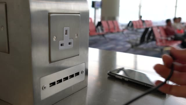 Traveler-charging-mobile-phone-battery-at-free-service-charging-station-at-International-Airport-