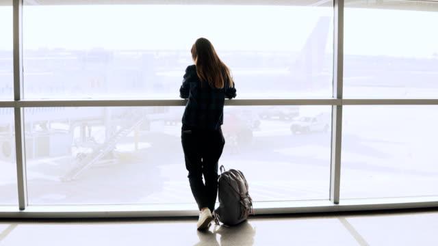 Niña-toma-selfie-foto-junto-a-la-ventana-de-aeropuerto-Turista-europeo-feliz-con-mochila-usa-smartphone-en-terminal-4K