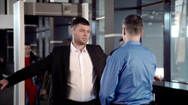 Hombre-de-negocios-pasando-el-control-de-la-frontera-con-detector-de-metales