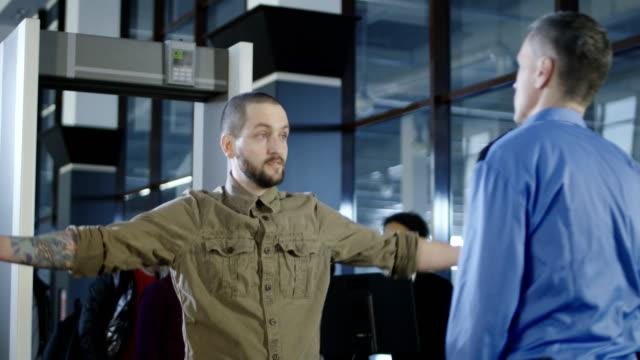 Trabajador-de-aeropuerto-control-de-pasajeros-con-detector-de-metales