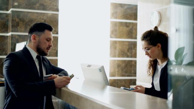 Geschäftsmann-Gast-im-Gespräch-mit-Empfangsdame-Mädchen-am-Schreibtisch-in-der-Rezeption-des-Hotels-stehen-und-Zahlung-Rechnung-mit-Kreditkarte-über-kontaktlose-Zahlungstechnologie-Wirtschaft-Reisen-und-Menschen-Konzept