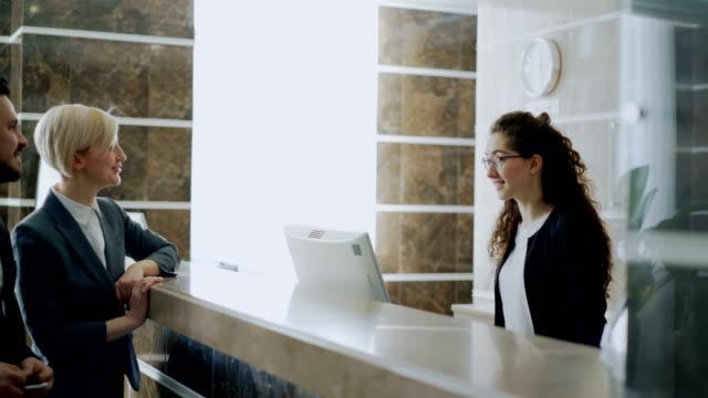 Unternehmer-und-Unternehmerin-Gäste-kommen-Angestellte-an-der-Rezeption-Mädchen-zu-zahlenden-Rechnung-mit-Kreditkarte-über-kontaktlose-Zahlungstechnologie-an-der-Hotelrezeption-Wirtschaft-Reisen-und-Menschen-Konzept