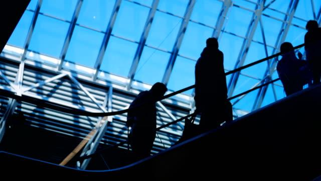 Siluetas-de-personas-en-escaleras-mecánicas-en-centro-comercial-con-grandes-ventanales