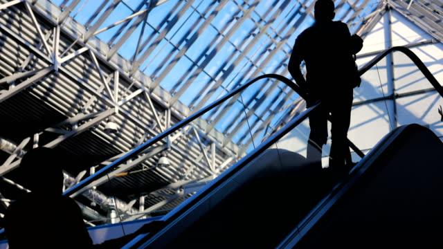 Vidrio-moderno-edificio-y-siluetas-de-personas-de-negocios-en-movimiento-en-escalera-mecánica