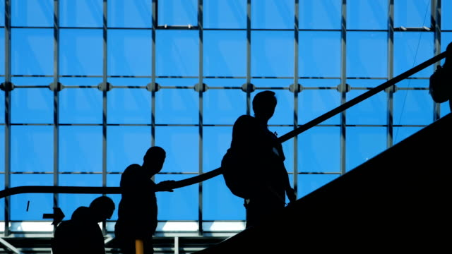 People-silhouettes-on-escalator-inside-of-shopping-mall-with-large-windows