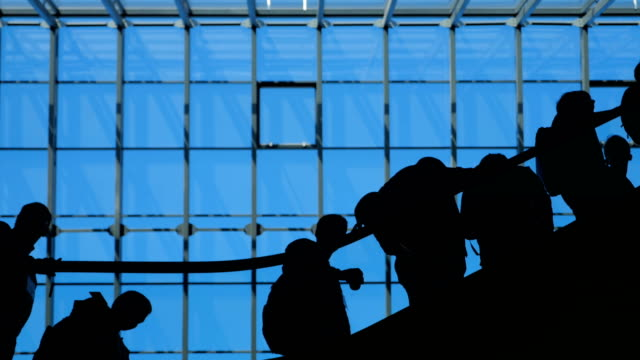 The-glass-window-airport-ecsalator-with-moving-silhouette-of-people