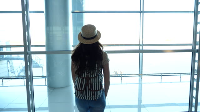 Young-woman-in-hat-with-backpack-coming-to-window-in-terminal-of-airport-and-looking-at-runway-Girl-waiting-for-her-airplane-Tourism-and-travel-concept-Rear-back-view-Close-up