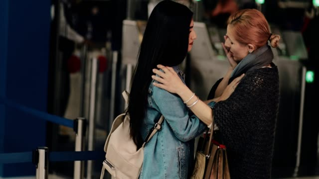 Mother-and-young-daughter-embracing-and-saying-goodbye-at-airport
