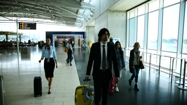 Multi-ethnic-travelers-with-suitcases-walking-at-international-airport