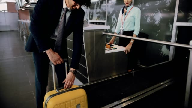 Young-man-weighing-suitcase-and-doing-check-in-at-airport