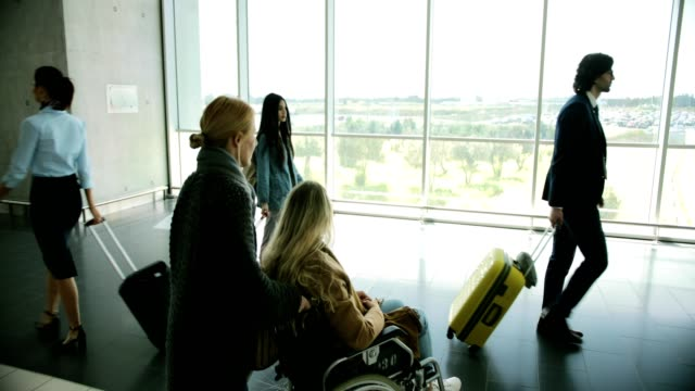 Young-disabled-woman-on-wheelchair-looking-out-airport-window