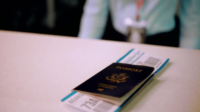 Traveler-s-passport-and-boarding-pass-on-airport-check-in-desk