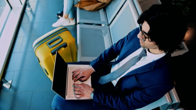 Young-businessman-using-laptop-while-waiting-to-board-on-airplane