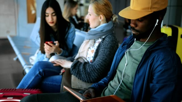 Multi-ethnic-travelers-sitting-on-bench-at-airport-gate