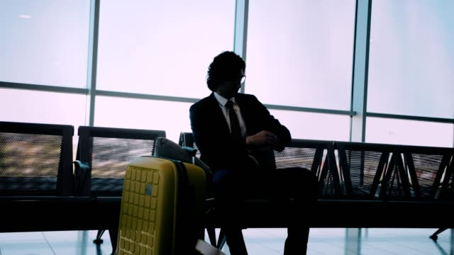 Businessman-sitting-on-bench-and-checking-the-time-at-airport