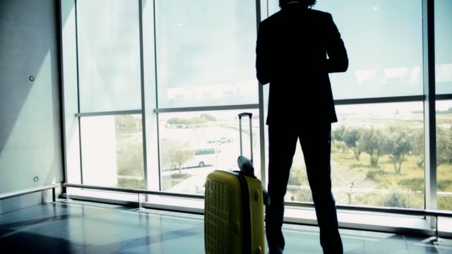 Young-businessman-checking-the-time-while-looking-out-airport-window