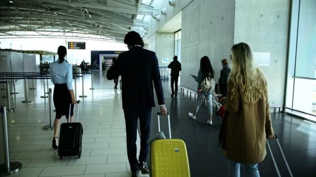Multi-ethnic-travelers-walking-on-airport-corridor-towards-gate