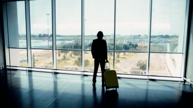 Young-businessman-in-suit-looking-out-international-airport-window