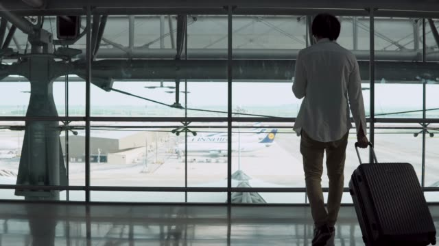 4K-Male-Young-passenger-using-smartphone-walking-with-suitcase-luggage-in-departure-area-of-airport-terminal-Asian-businessman-in-casual-clothing-on-business-trip-Modern-travel-lifestyle-concepts-