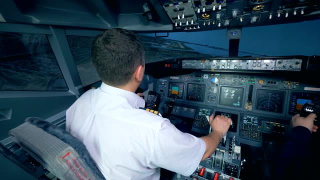 Two-airmen-in-flight-simulator-holding-helms-in-a-cockpit-4K-