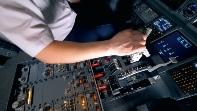 One-pilot-holds-his-hand-on-a-plane-lever-in-a-flight-simulator-4K-
