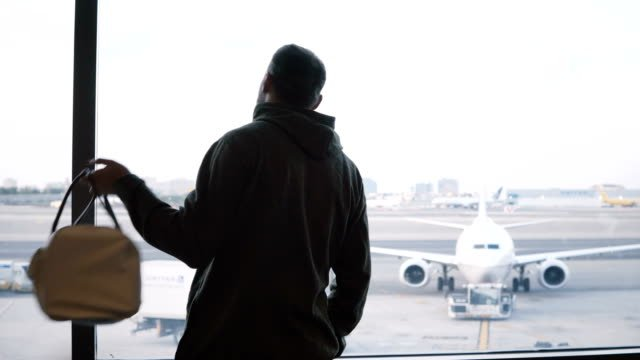 Male-traveler-with-big-bag-on-shoulder-walking-up-to-airport-lounge-terminal-window-to-enjoy-the-view-of-planes-and-cars