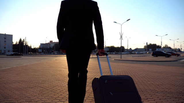 Unrecognizable-businessman-in-black-suit-is-late-for-the-flight-and-quickly-going-with-his-suitcase-to-airport-Young-man-looking-at-his-watch-and-in-hurry-walking-with-luggage-to-terminal-Rear-view