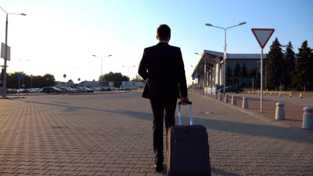 Dolly-la-foto-de-la-joven-confía-en-un-formal-traje-negro-caminando-con-su-equipaje-en-calle-urbana-Próspero-hombre-de-negocios-va-a-la-terminal-del-aeropuerto-y-tirando-de-maleta-sobre-ruedas-al-atardecer-Cierre-para-arriba
