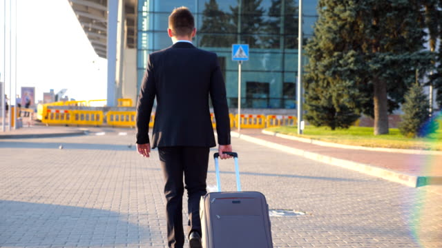 Vista-posterior-del-empresario-joven-irreconocible-caminando-a-la-terminal-del-aeropuerto-y-tirando-de-maleta-sobre-ruedas-al-atardecer-Negocio-exitoso-hombre-persona-con-su-equipaje-en-la-calle-de-la-ciudad-Cierre-para-arriba