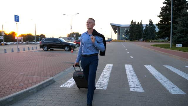Hombre-joven-caminando-sobre-medio-ambiente-urbano-con-una-chaqueta-sobre-sus-hombros-y-tirando-de-maleta-con-ruedas-Hombre-de-negocios-acertado-ir-con-equipaje-desde-el-aeropuerto-en-la-calle-de-la-ciudad-Cerrar-tiro-Dolly
