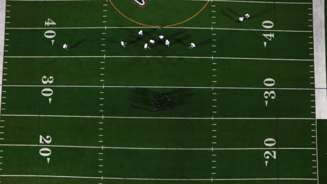 The-camera-spins-from-above-as-a-football-team-in-a-huddle-gets-hyped-before-a-game