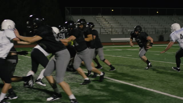 A-football-player-pushes-down-opponents-right-before-making-a-touchdown