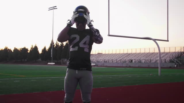 Portrait-of-a-football-player-putting-on-his-helmet