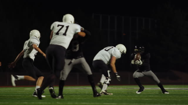 A-football-player-struggles-to-get-past-his-opponents-and-runs-toward-the-end-zone