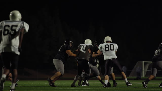 A-football-player-fights-his-way-down-the-field-toward-the-end-zone-at-night