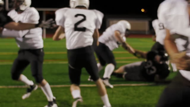 A-football-player-gets-the-ball-handed-off-to-him-and-he-makes-a-touchdown