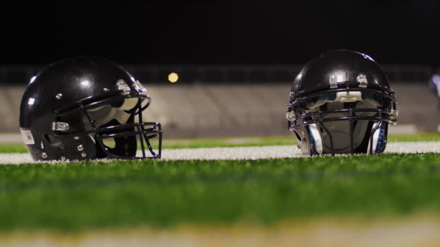 Close-up-of-two-football-helmets-on-the-field-with-players-walking-through-the-foreground