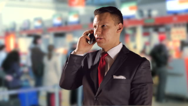 Airport-Business-Man-on-Mobile-Phone-Talking-and-Travel-Red-Tie-and-Suit