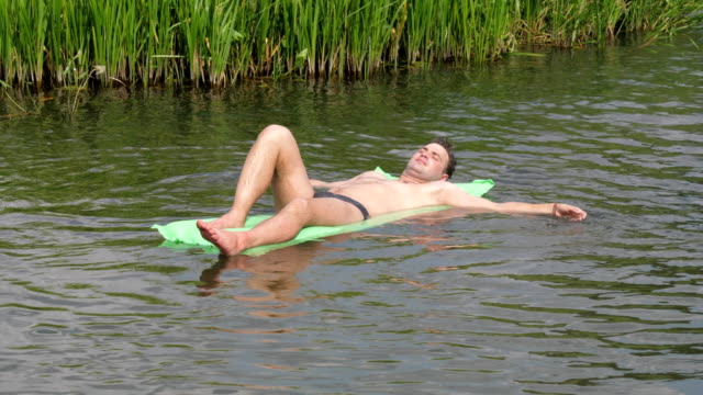 Resting-The-Man-In-The-Hot-Summer-Day-Swimming-In-The-River-On-The-Mattress-