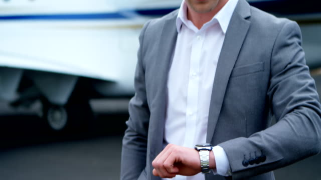 Businessman-checking-time-while-standing-on-a-runaway-4k